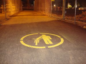 This unusual sign that has appeared on the Alexander Street 'temporary walking path' seems to indicate that cyclists must walk their bikes. (click to expand.)